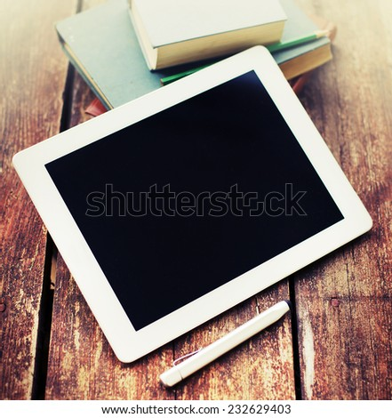 Blank modern digital tablet with books and pencil on a wooden desk. Digital tablet computer with isolated screen on wooden table  - stock photo