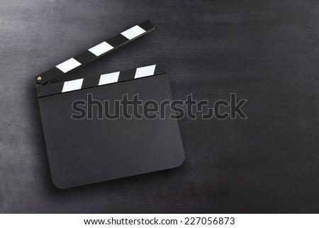 Blank movie clapper board on a chalkboard background - stock photo