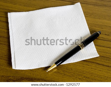 Blank napkin for your message on wooden table and a pen - stock photo