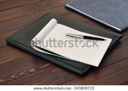 Blank note book and pen on leather folder on the office desk. Top view - stock photo