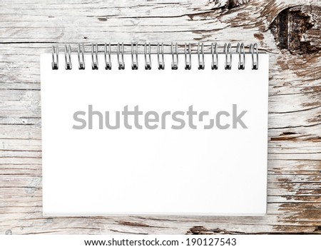 Blank note book on grunge wood - stock photo