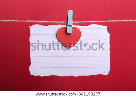 Blank note paper with red heart hanging against red background. - stock photo