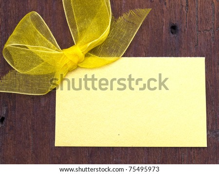 blank note with yellow bow on the wooden background - stock photo