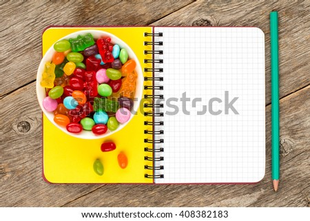 Blank notebook and bowl with mixed candies - stock photo