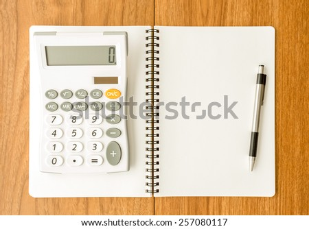 Blank notebook and calculator on wood background - stock photo