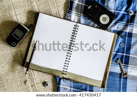 Blank Notebook and old technology devices background - stock photo