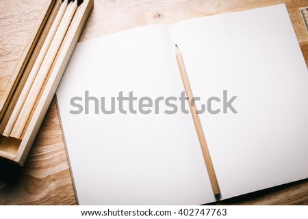 Blank notebook and pencil on wooden table - stock photo