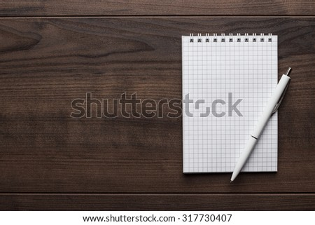 blank notebook and white pen on the brown wooden table - stock photo