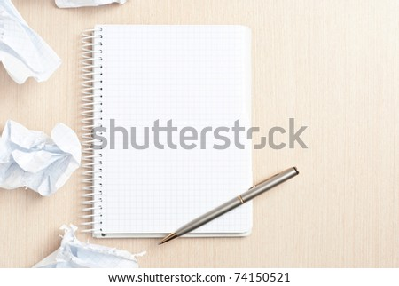 Blank notebook page and crumpled paper wads on desk - stock photo