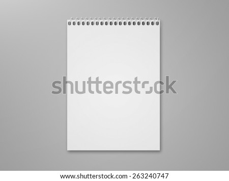 Blank notebook sketch pad with metal spiral with lots of copy space, isolated on a gray background with shadow. - stock photo