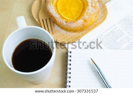 Blank notebook with orange tart ,coffee on the wooden desk - stock photo
