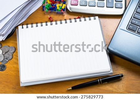 Blank notebook with part of laptop, receipts and calculator - stock photo