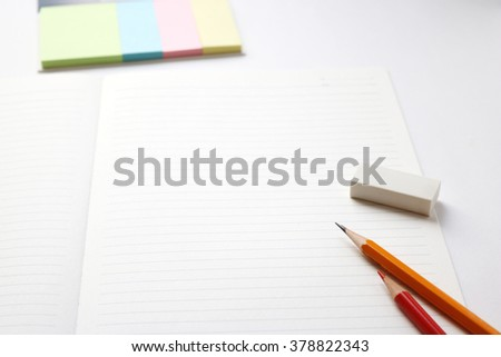 Blank notebook with pencil, eraser, red pencil and tag paper on white background. - stock photo