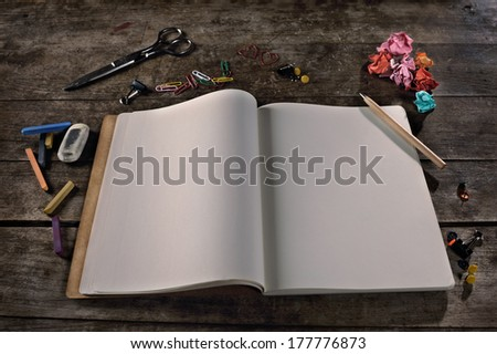 Blank notebook with pencil, paper clips, and other office supplies (chalk pastels, eraser, scissor, thumbtacks) on vintage background. It can be easily customized with any text.  - stock photo