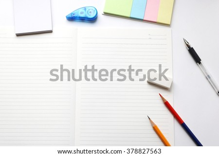 Blank notebook with pencil, red pencil, tag paper, notepad, correction tape, and eraser on white background. - stock photo