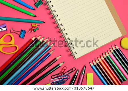 Blank notebook with school supplies on pink background - stock photo