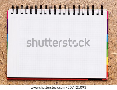 Blank notebook with spiral bind spine on a wood background - stock photo