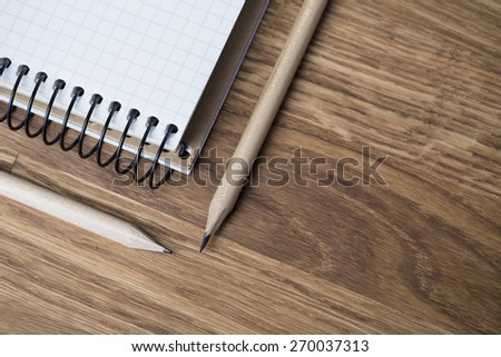 Blank notebook with two pencils on an oak wood table - stock photo