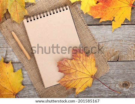 Blank notepad and colorful autumn maple leaves on wooden table background - stock photo