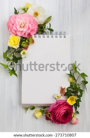 Blank notepad and flowers over white wooden background. Top view with copy space - stock photo