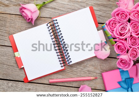 Blank notepad and gift box full of pink roses over wooden table. Top view with copy space - stock photo