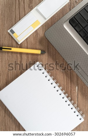 Blank notepad and laptop on office wooden table, top view - stock photo