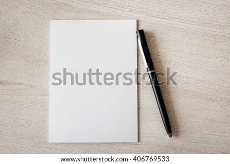 Blank notepad and pen on wooden table - stock photo