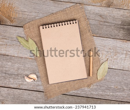 Blank notepad for copy space and herbs on wooden table - stock photo