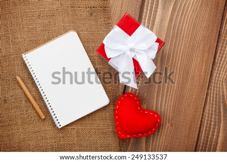 Blank notepad for copy space and vintage handmaded valentines day toy heart over wooden background - stock photo