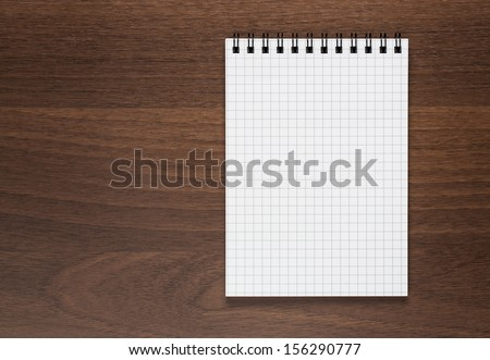 Blank notepad, notebook at the wooden desk with copy space - stock photo