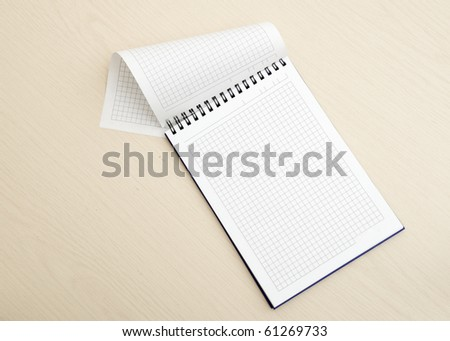 Blank notepad on wood table - stock photo