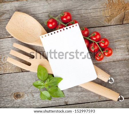 Blank notepad paper for your recipes with tomatoes and basil on wooden table - stock photo