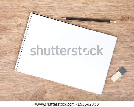 Blank notepad, pencil and eraser on the wooden table. View from above - stock photo