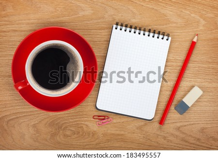 Blank notepad with office supplies and red coffee cup on wooden table. Above view - stock photo