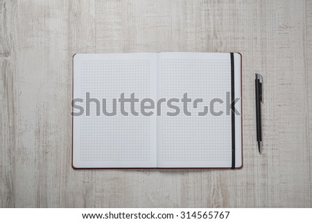 Blank notepad with pen and pencil on office wooden table. - stock photo