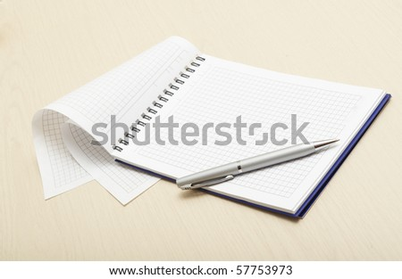 Blank notepad with pen on wood table - stock photo