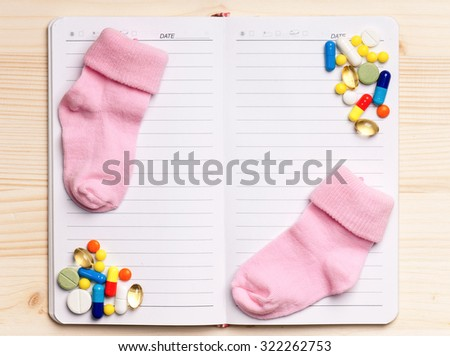 Blank notepad with pills on the wooden table. View from above - stock photo
