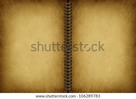 Blank old note book with an antique weathered grunge parchment texture as an empty beige vintage pad with a metal coil in the middle. - stock photo