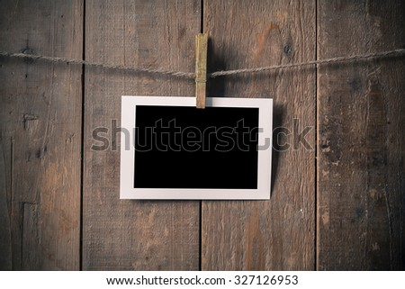 Blank Old Photo Frame Hanging on a Rope By Clothespin on Wood Background , Vintage Style - stock photo