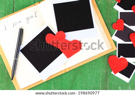 Blank old photos and decorative hearts on old notebook, on color wooden background - stock photo