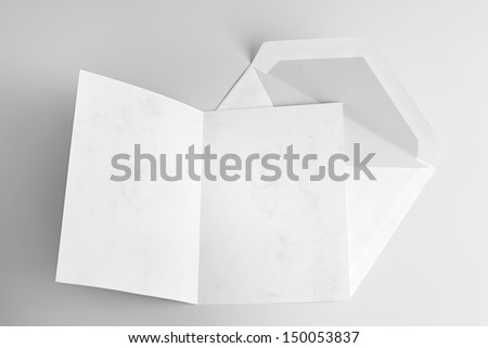 Blank open card and envelope over grey background with shadow - stock photo