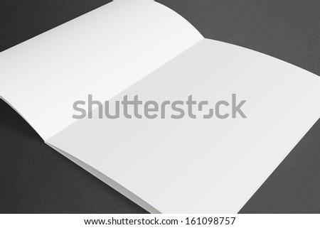 Blank opened Magazine on dark Background - stock photo