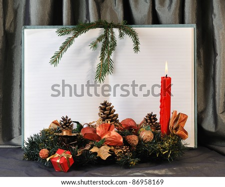 blank pages of old open notebook bordering with christmas decoration and red burn candle - stock photo
