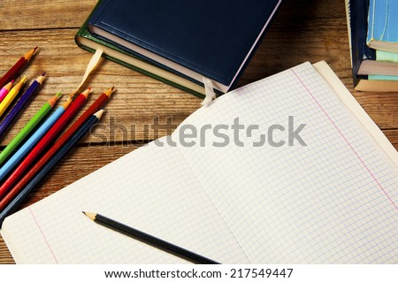 Blank paper and colorful pencils, on the wooden table. View from above. School concept. - stock photo