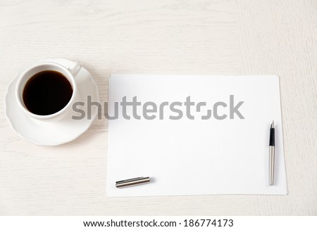 Blank paper and pen on wooden table - stock photo