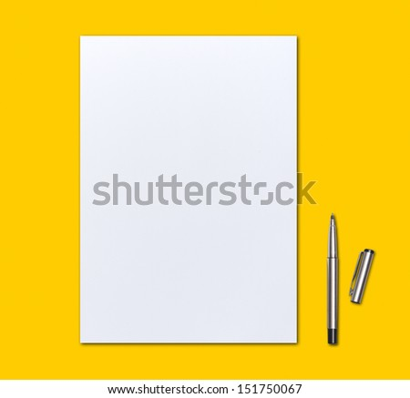 blank paper and pen on yellow background - stock photo