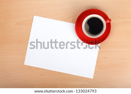 Blank paper and red coffee cup on wood table - stock photo