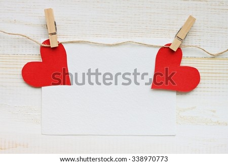 Blank paper card decorated with hearts, romantic background for writing love note. Bright red paper hearts pinned on twine.   - stock photo