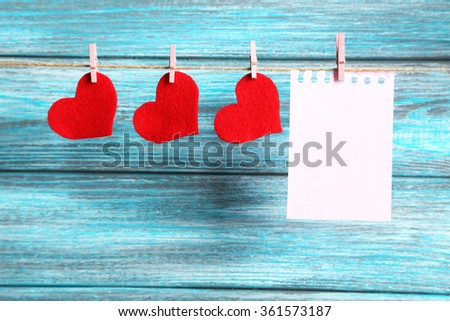 Blank paper hanging on rope on blue wooden background - stock photo