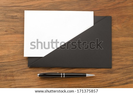 Blank paper in black folder and pen on wooden background   - stock photo